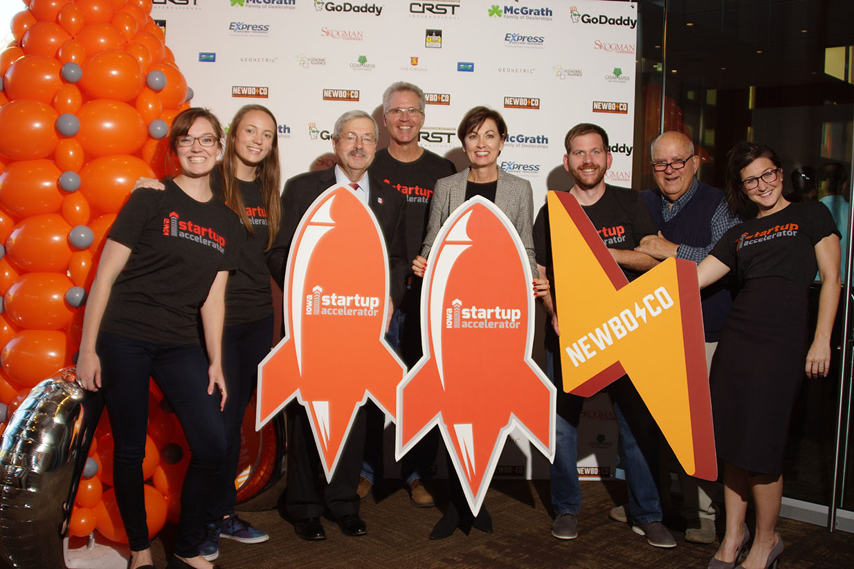 NewBoCo staff poses with rocketship and lightning bolt cutouts (NewBoCo's icons) at an event with the Iowa Lieutenant Governor in 2016