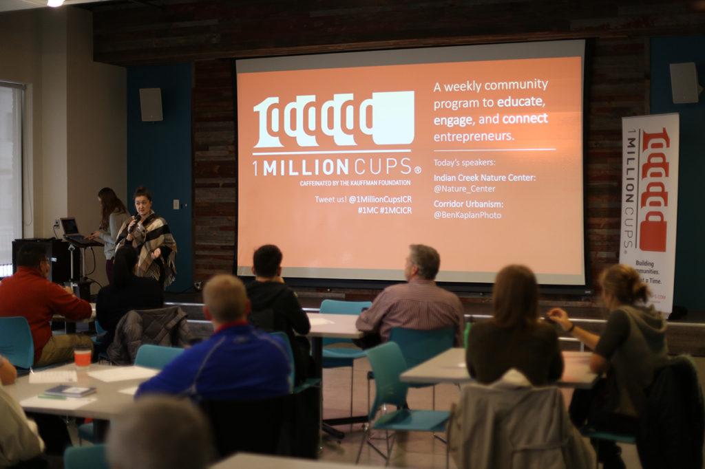A gathered crowd listens to a presenter at a 1 Million Cups Cedar Rapids event
