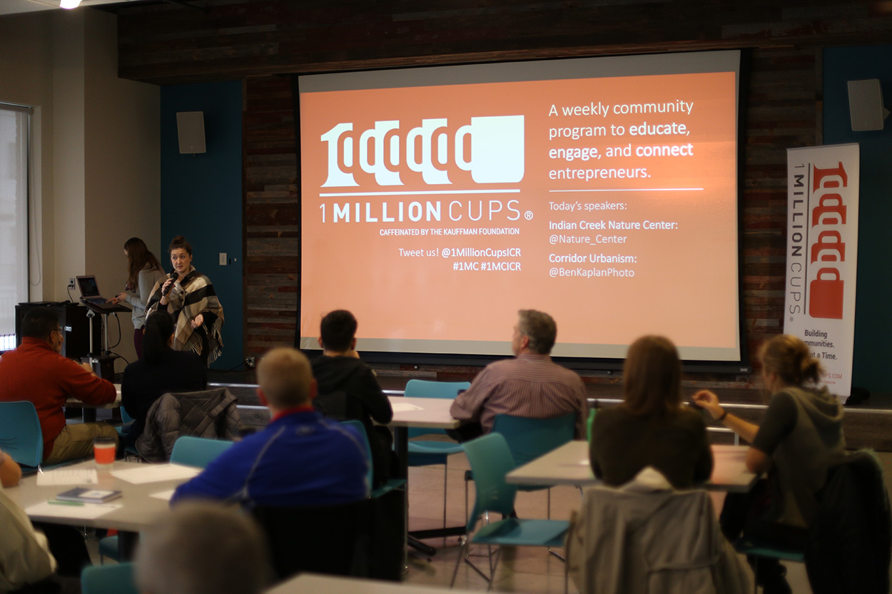 A gathered crowd listens to a presenter at a 1 Million Cups Cedar Rapids event