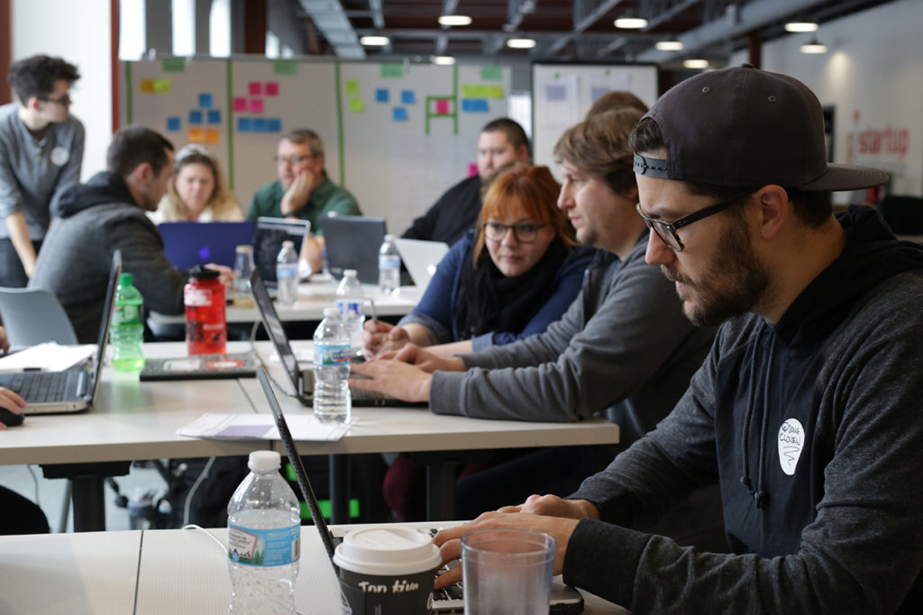 A host of DeltaV students huddle over their laptops in an open environment