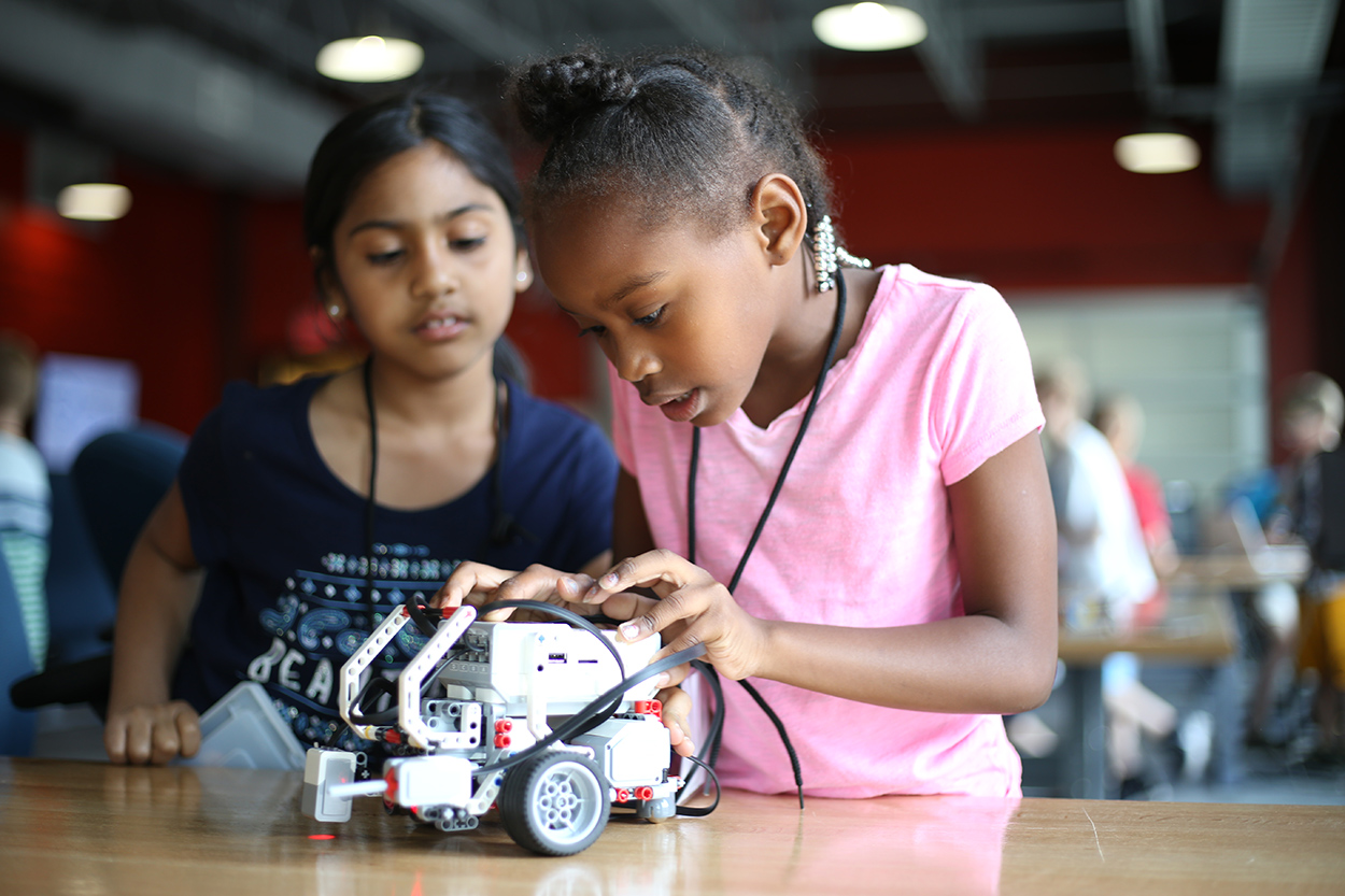 Two female students work on building a robot.