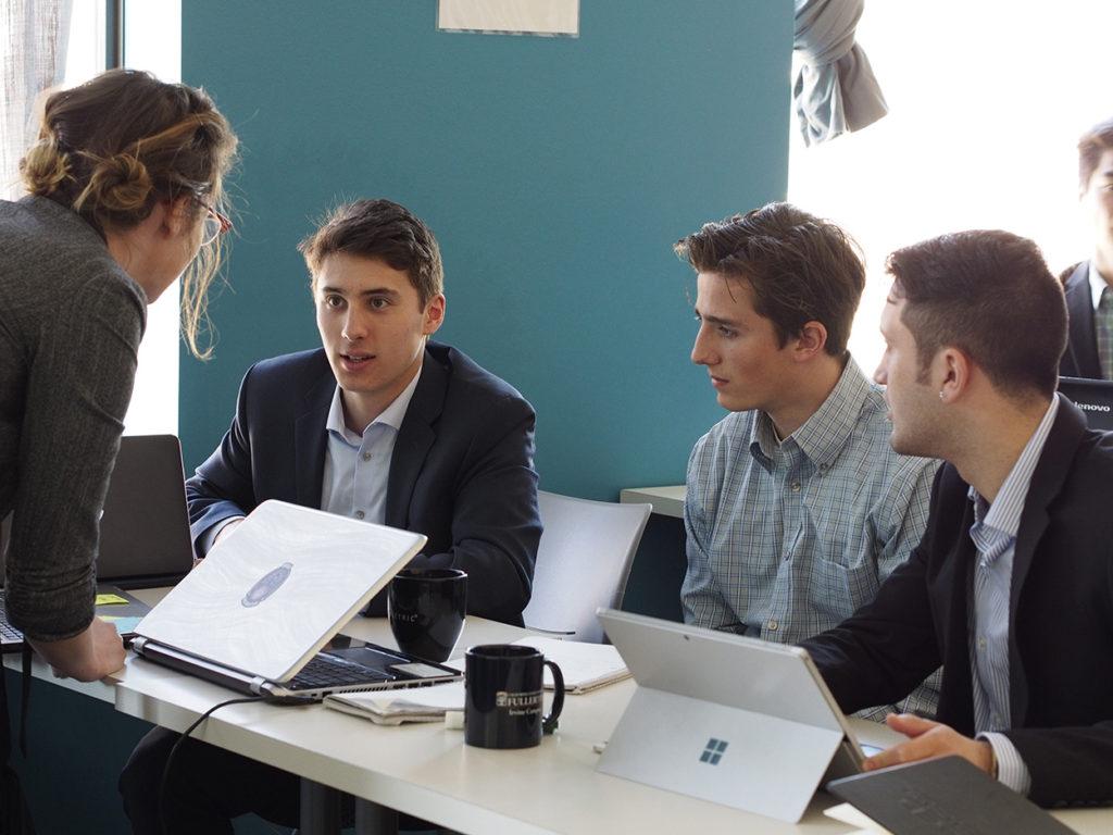 Three members of an accelerator organization converse with a NewBoCo representative