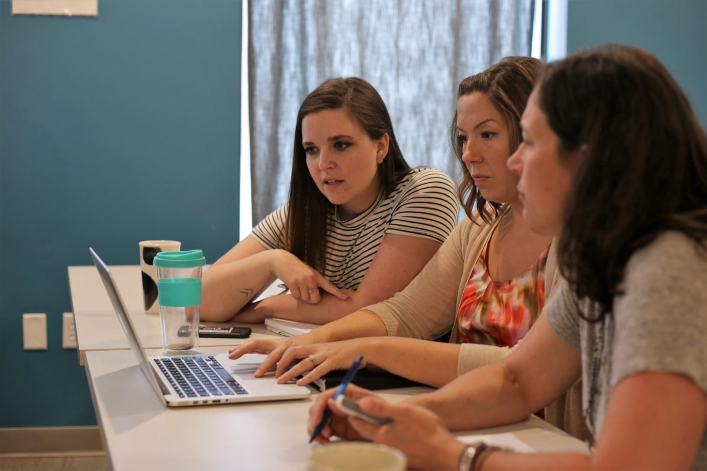 Members of Girls With Ideas, an ISA portfolio team, look at a laptop.