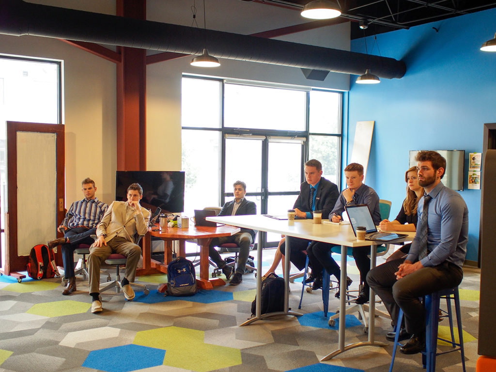 Startup Accelerator members gather at tables for a work session in one of the Geonetric building's colorful common areas