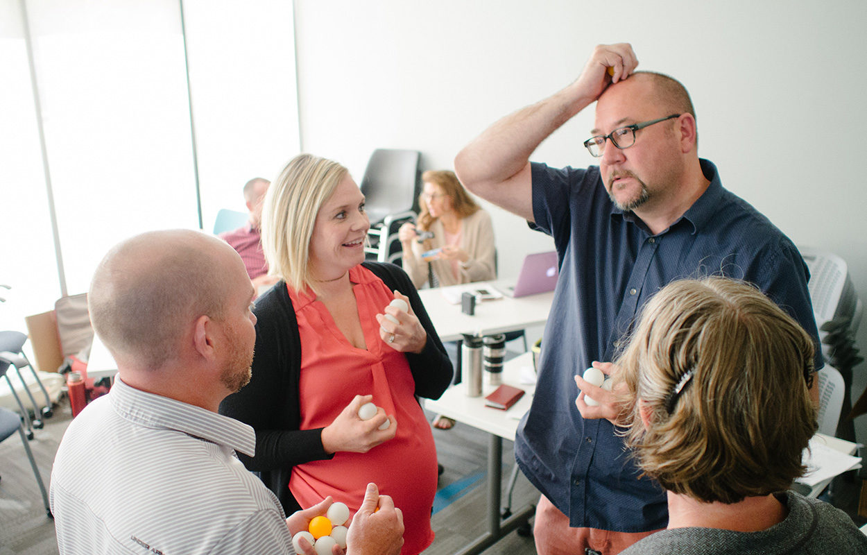 """Agile workshop participants gather in a circle and discuss the """"Agile Ball Game"""" they are playing"""