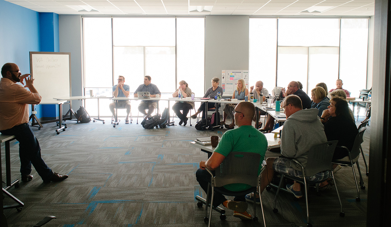 A large group sits in a semi-circle in a well-lit conference room and listens to an Agile speaker