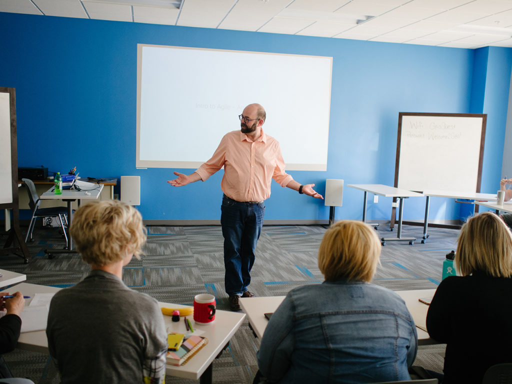 Agile coach, Nate Adams, stands before a group of eager students, arms outstretched inquisitively