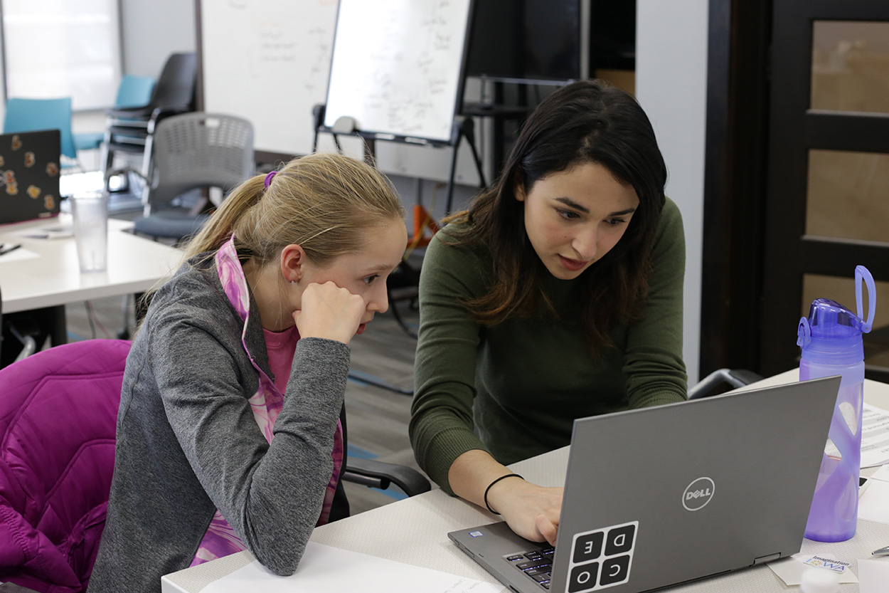 NewBoCo Volunteer Asmaa Elkeurti works with a student on a laptop for NewBoCo's Girls Code Camp