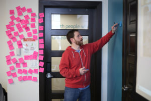 Chief Relationship Officer, David Tominksy posts sticky notes to a wall as he leads a customer discovery workshop