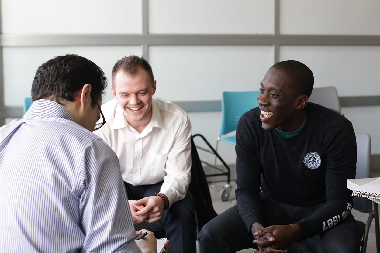 Three people early in the Accelerator process joyfully discuss their goals for the program
