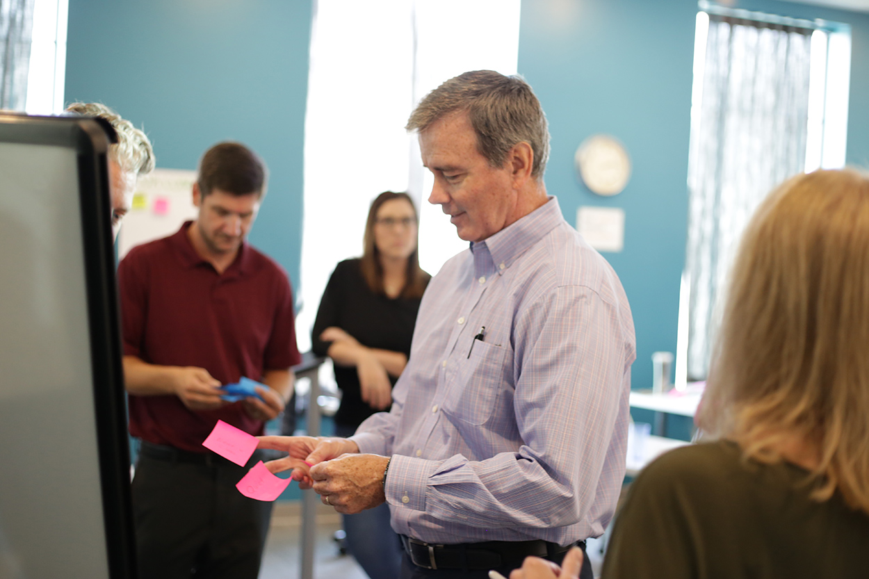An Innovation workshop participant handles two Post-It notes as they struggle to prioritize objectives