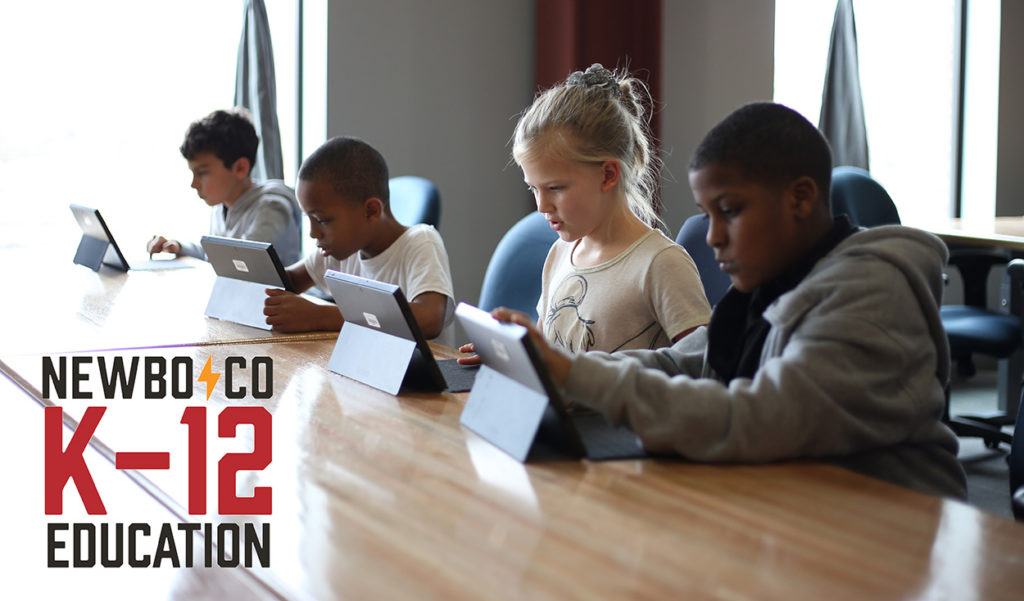Four kids work on laptops learning how to code with the NewBoCo K-12 Education logo in the bottom left corner.