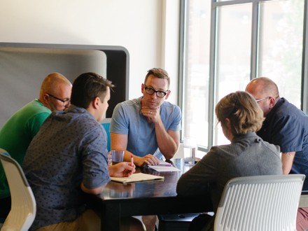 A group of five people gather around a table discussing agile