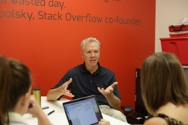 Frank Camp, NewBoCo General Counsel, sits at a table with two women working on a startup