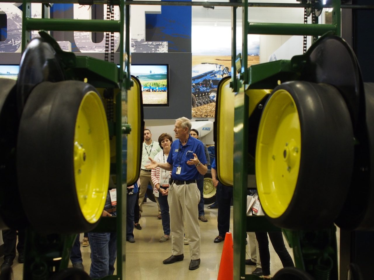 A docent stands between two rows of agriculture equipment and talks to a crowd in the Kinze Innovation Center.