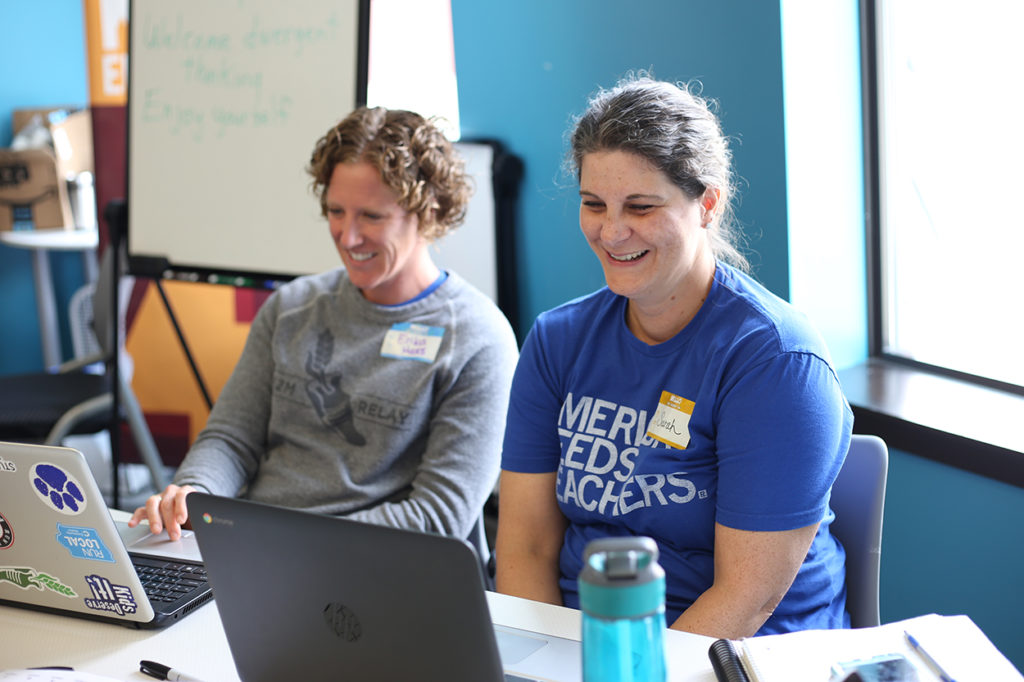 Two teachers smiling and laughing as they learn about tech education at their laptops