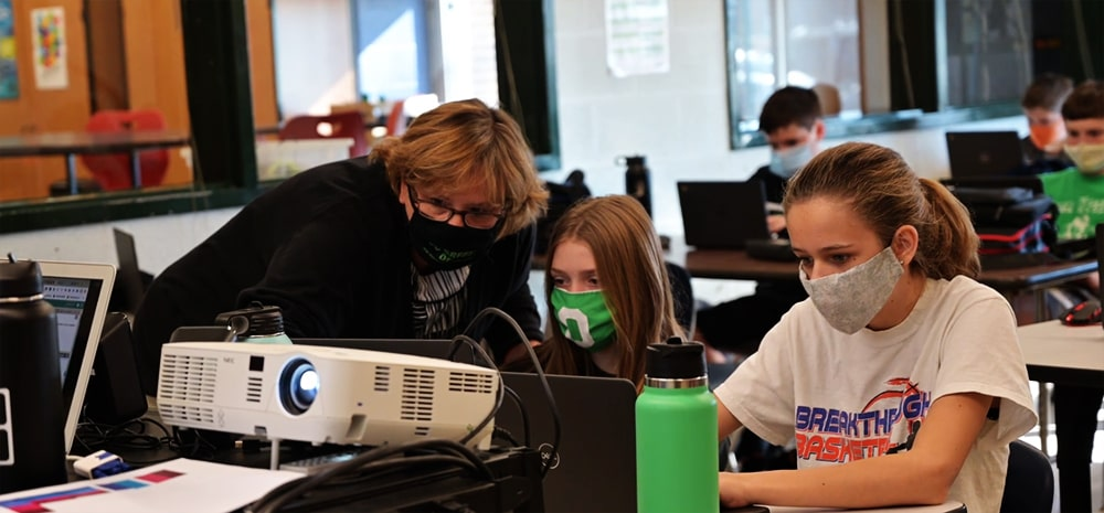 A masked teacher and students practice Osage County's new computer science curriculum