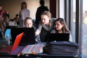 A volunteer guides two younger students through exercises on their laptops through a CoderDojo event