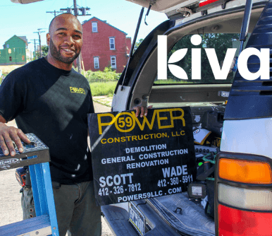 Thanks to a Kiva loan, an entrepreneur poses beside their new construction business