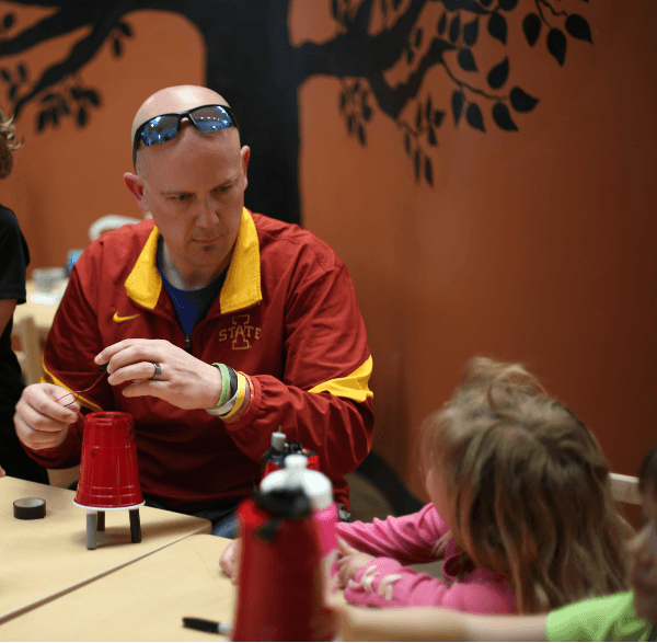 NewBoCo Executive Director, Aaron Horn, aides children in assembling a robotics project using a plastic cup and markers