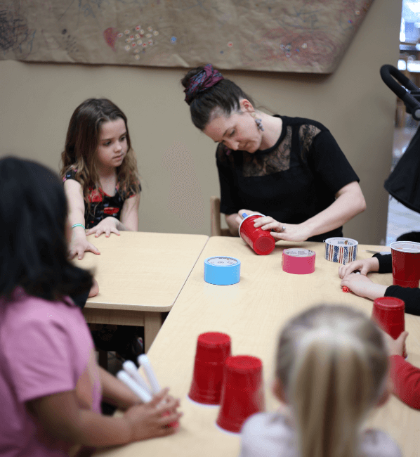 Kaitlin Byers, NewBoCo's Director of Development, assembles a child's project as other children observe