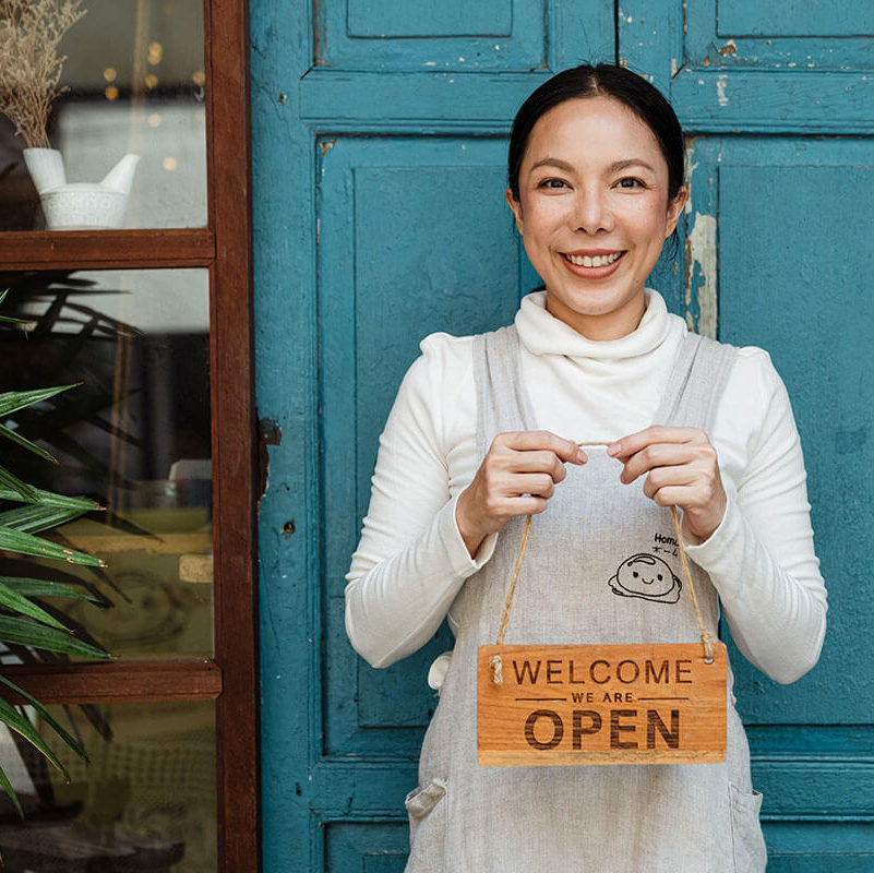 A woman stands proudly in front of her new small business.