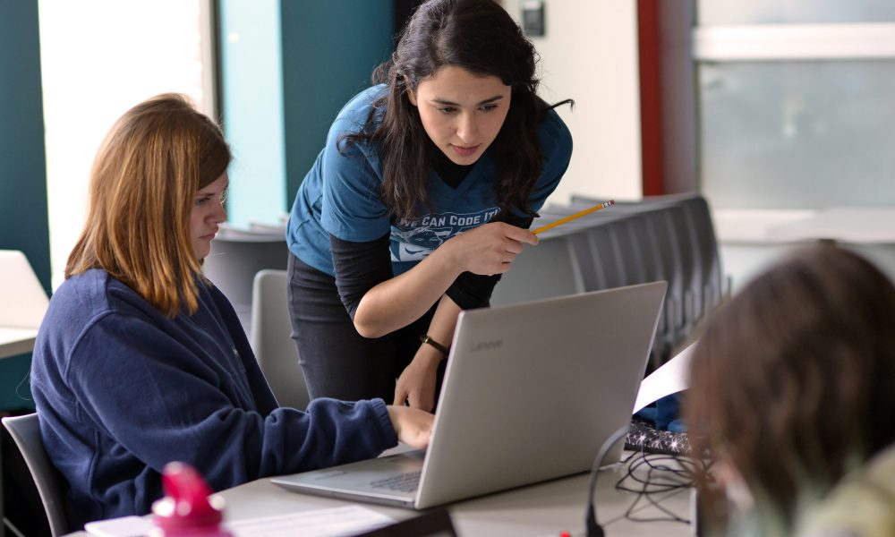 A volunteer guides a young student through an GirlsCode++ exercise. These efforts are made possible, in part, thanks to generous donations.