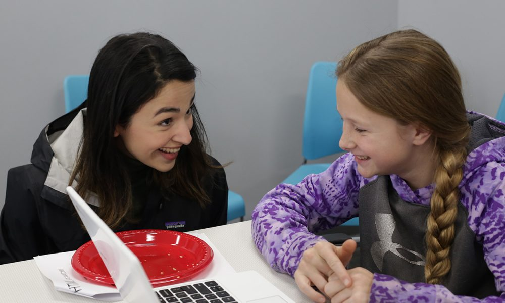 Two students chat excitedly over an accomplishment in CoderDojo