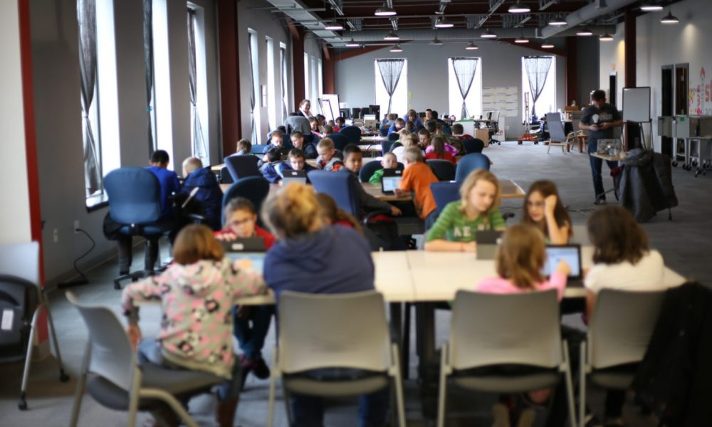 A NewBoCo conference room filled with kids and parents at round tables during a CoderDojo event