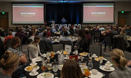 Attendees gather in a conference room around set tables as Rick Cushman presents at NewBoCo's Annual Meeting.